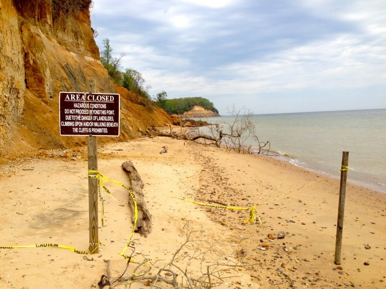 The beach is closed at the base of the cliffs, but people can walk by if they walk in the water.