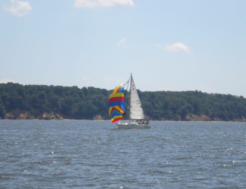 Sailboat sailing downwind using a brightly colored spinnaker