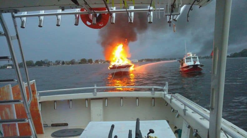 Solomon's Island burning boat being towed behind charter boat